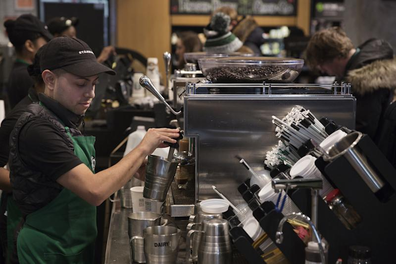 A barista froths milk for a drink inside a Starbucks shop in New York. Shareholders of the company are criticizing how its employee benefits are different for hourly workers and salaried workers. (Bloomberg via Getty Images)