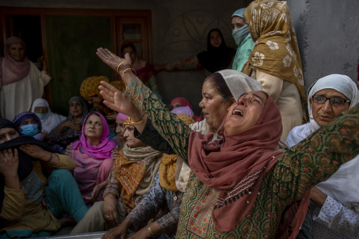Relatives wail during the funeral of Waseem Ahmed, a policeman who was killed in a shootout, on the outskirts of Srinagar, Indian controlled Kashmir, Sunday, June 13, 2021. Two civilians and two police officials were killed in an armed clash in Indian-controlled Kashmir on Saturday, police said, triggering anti-India protests who accused the police of targeting the civilians. (AP Photo/ Dar Yasin)