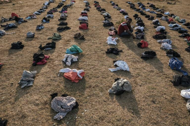 A displaced person sits among piles of clothes being distributed at the camp in Chagni