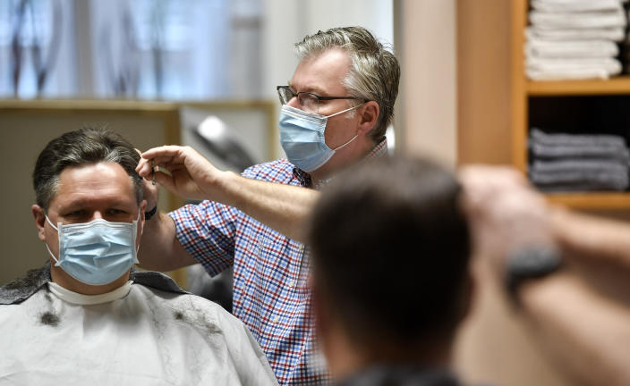 Hairdresser Holger Augustin cuts hair of a customer at his barber shop in Gelsenkirchen, Germany, Monday, March 1, 2021. Hairdressers across Germany have reopened for business this morning after a more than 2-month closure, another cautious step as the country balances a desire to loosen restrictions with concern about the impact of more contagious coronavirus variants. (AP Photo/Martin Meissner)