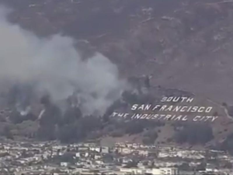 The South San Francisco The Industrial City sign as the fire approached it along vegetation ((Daniel Swain - Twitter))