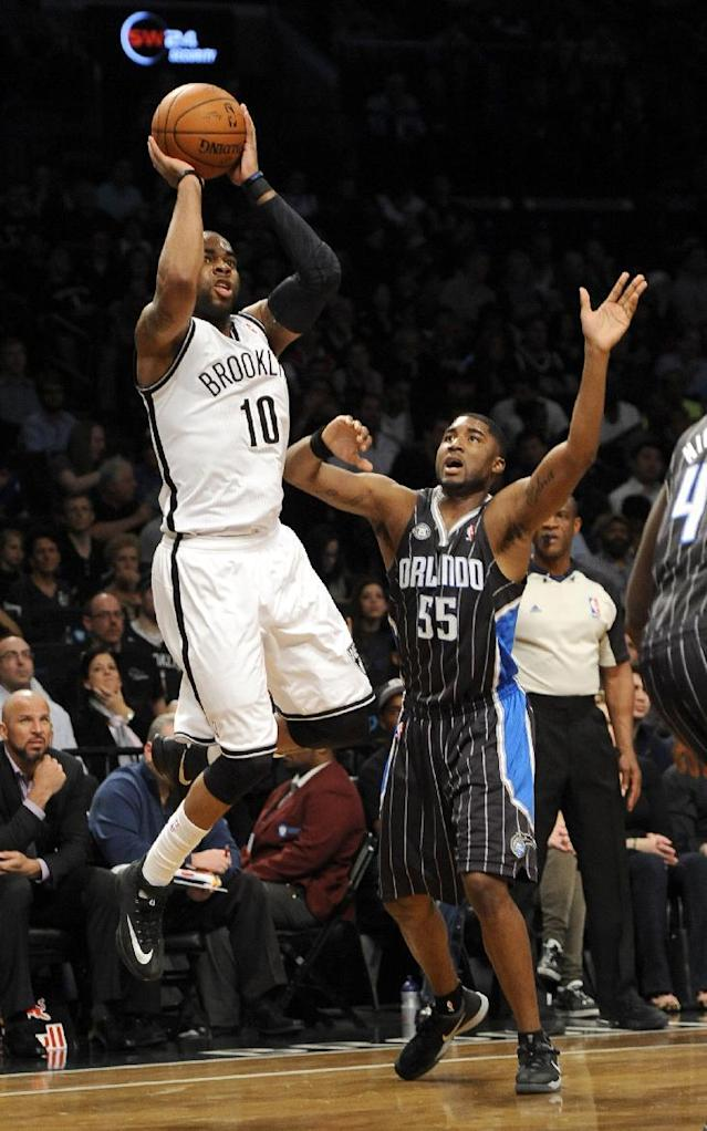 Brooklyn Nets' Marcus Thornton (10) shoots in front of Orlando Magic's E'Twaun Moore (55) during the first half of an NBA basketball game Sunday, April 13, 2014, in New York. (AP Photo/Kathy Kmonicek)