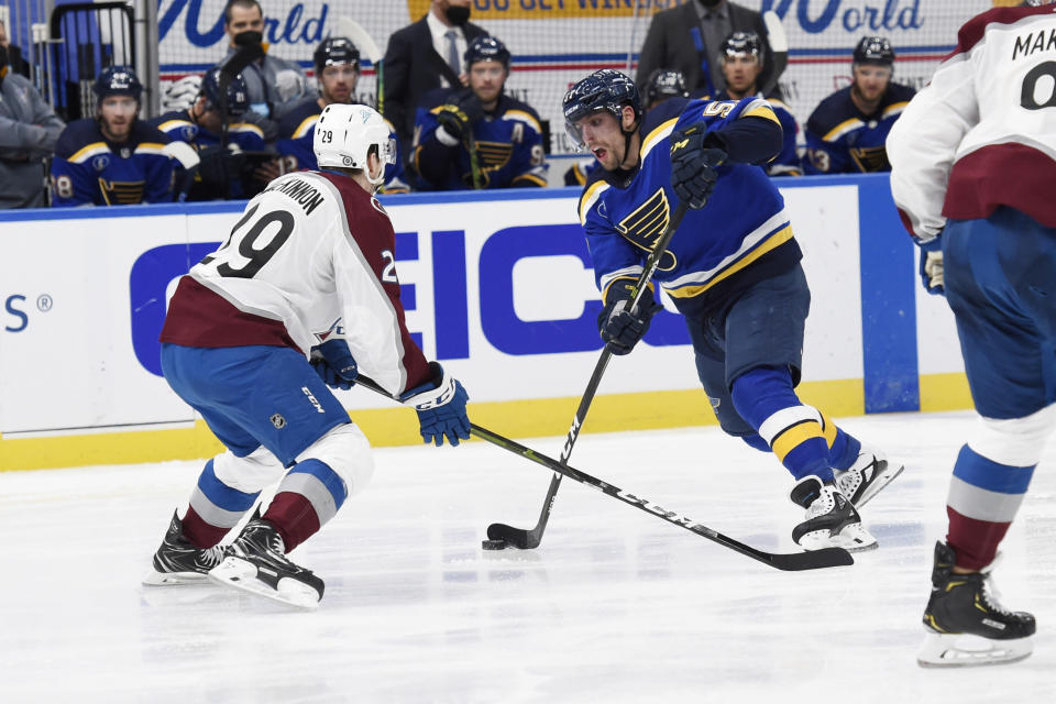 Colorado Avalanche's Nathan MacKinnon (29) defends against St. Louis Blues' David Perron (57) during the second period of an NHL hockey game on Wednesday, April 14, 2021, in St. Louis. (AP Photo/Joe Puetz)
