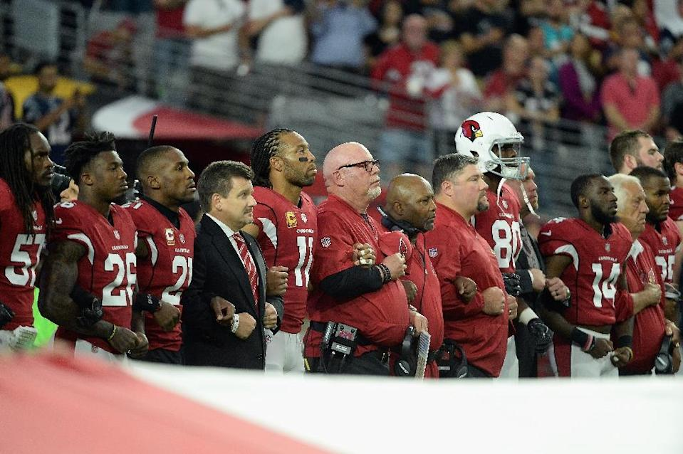 Wide receiver Larry Fitzgerald (C-L) and head coach Bruce Arians (C-R) of the Arizona Cardinals link arms during the National Anthem before the start of the NFL game on September 25, 2017 in Glendale, Arizona (AFP Photo/Jennifer Stewart)