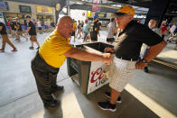 Tom Congdon, left center, a vendor at Pittsburgh sports venues for 38 years, mans his beer and water cart in the concourse at PNC Park during a baseball game between the Pittsburgh Pirates and the Atlanta Braves in Pittsburgh, Monday, July 5, 2021. A majority of teams have now opened their parks to full capacity, and the rest are scheduled to do so soon. That could mean more good news for ballpark workers. (AP Photo/Gene J. Puskar)