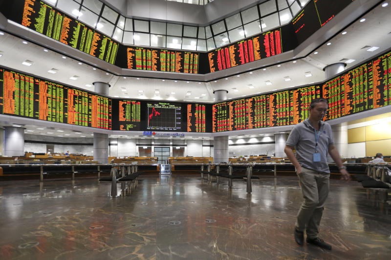 Visitor walk under a stock trading board at a private stock market gallery in Kuala Lumpur, Malaysia, Friday, Jan. 11, 2019. Asian markets were mostly higher on Friday as investors cheered a more reactive Federal Reserve and U.S.-China trade talks.(AP Photo/Vincent Thian)