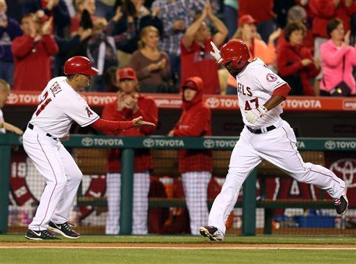 Los Angeles Angels Howie Kendrick, right, is congratulated by third base coach Dino Ebel after hitting a two-run home run in the fourth inning of a baseball game in Anaheim, Calif., on Tuesday, April  23, 2013. (AP Photo/Christine Cotter)