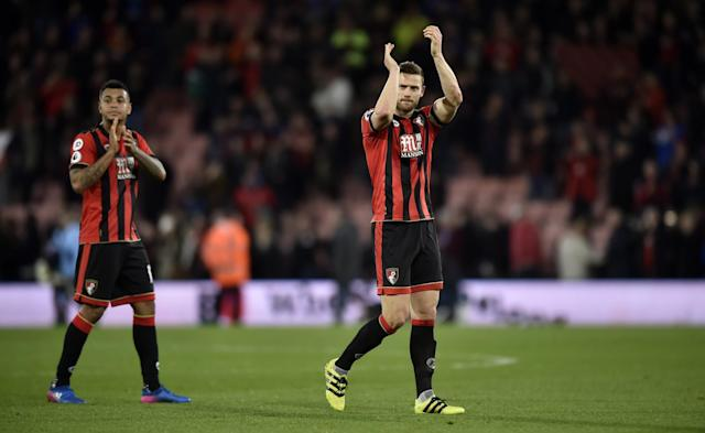 <p>Bournemouth's Joshua King and Simon Francis applaud fans after the game </p>