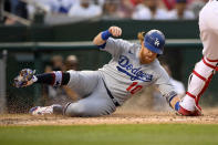 Los Angeles Dodgers' Justin Turner (10) slides home to score during the fourth inning of the team's baseball game against the Washington Nationals, Saturday, July 3, 2021, in Washington. (AP Photo/Nick Wass)
