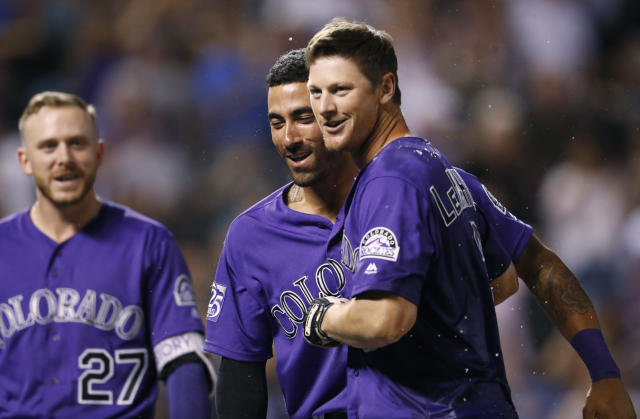 Colorado Rockies' DJ LeMahieu, right, is congratulated after hitting a two-run home run by Ian Desmond, center, and Trevor Story to defeat the Arizona Diamondbacks in the ninth inning of a baseball game, Wednesday, Sept. 12, 2018, in Denver. The Rockies won 5-4. (AP Photo/David Zalubowski)