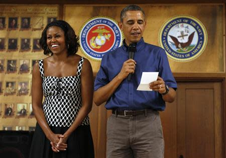 First lady Michelle Obama smiles as U.S. President Barack Obama speaks to military personnel during a Christmas day visit to Marine Corps Base Hawaii in Kaneohe, Hawaii December 25, 2013. REUTERS/Kevin Lamarque