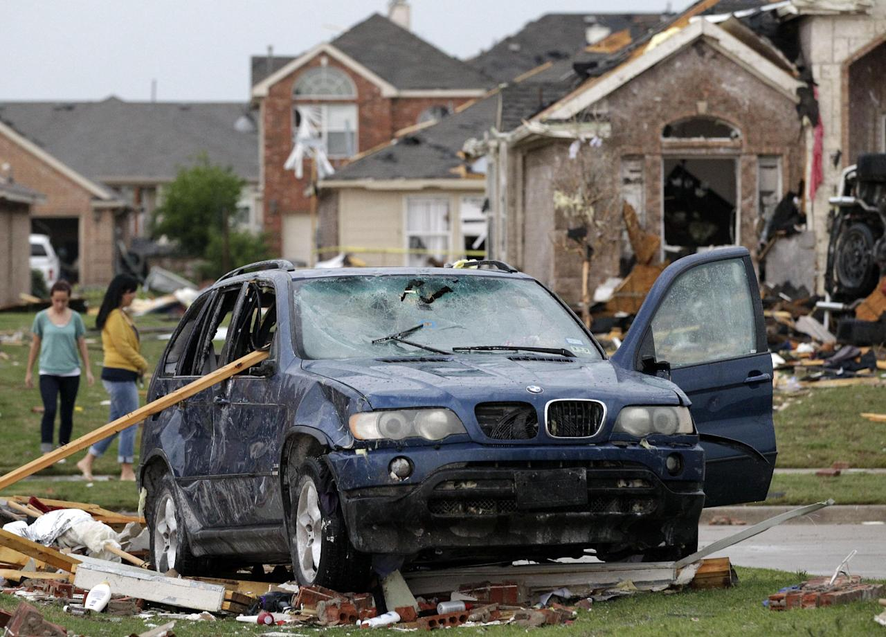 A damaged vehicle is seen as area residents survey the tornado damage to their neighborhood Tuesday, April 3, 2012, in Forney, Texas. Tornadoes tore through the Dallas area Tuesday, peeling roofs off homes, tossing big-rig trucks into the air and leaving flattened tractor trailers strewn along highways and parking lots. (AP Photo/Tony Gutierrez)