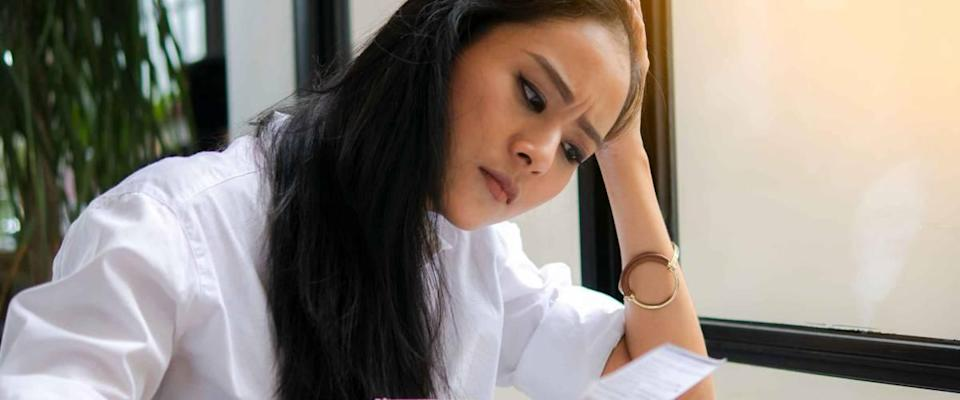 young woman holding papers looking stressed
