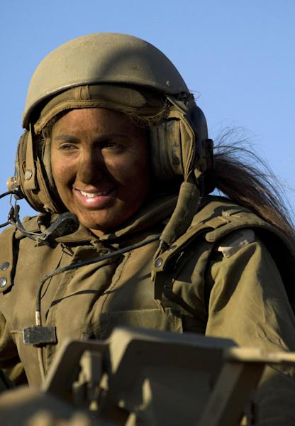 FILE - In this Wednesday, Sept. 19, 2012 file photo an Israeli female soldier sits on top of an armored personnel carrier during a military exercise in the Israeli-controlled part of the Golan Heights. From France's Joan of Arc, to female resistance fighters of World War II and the black-clad women warriors of the Viet Cong, popular history is filled with stories of women fighting alongside men in epic struggles. The image of the gun-toting Israeli woman warrior is widely seen as the prototype of a gender-blind military. Reality is different. Israeli women are subject to the draft — serving two years while men serve three. But women were barred from direct combat until 2000, when the first and so far only mixed gender infantry battalion was organized. (AP Photo/Ariel Schalit, File)