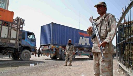 A Pakistani Frontier Constable (right) and Afghan National Army serviceman (left) keep watch as NATO supply trucks cross the Pakistan-Afghan border in Chaman on July 12. Islamabad agreed to reopen land routes for NATO goods on July 3 after ordering the longest border closure of the 10-year war in neighbouring Afghanistan in protest at botched US air raids that killed 24 Pakistani troops