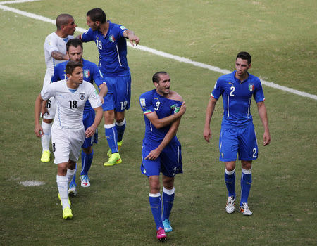 Italy's Chiellini shows shoulder, claiming he was bitten by Uruguay's Suarez, during 2014 World Cup Group D soccer match at the Dunas arena in Natal