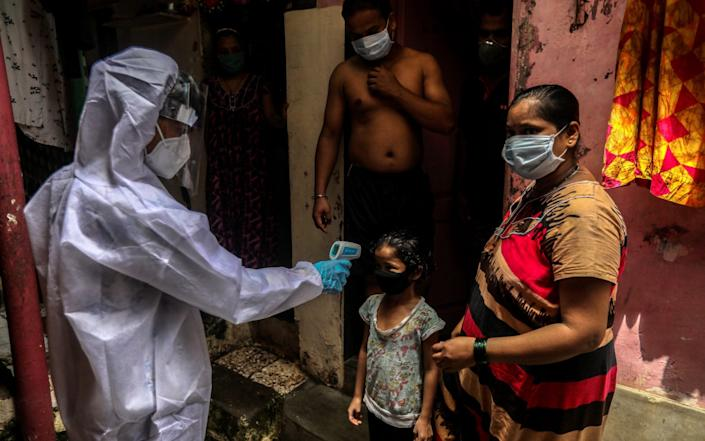 "A health worker checks the temperature of the residents of a ""containment zone"" Mumbai, India - Shutterstock"