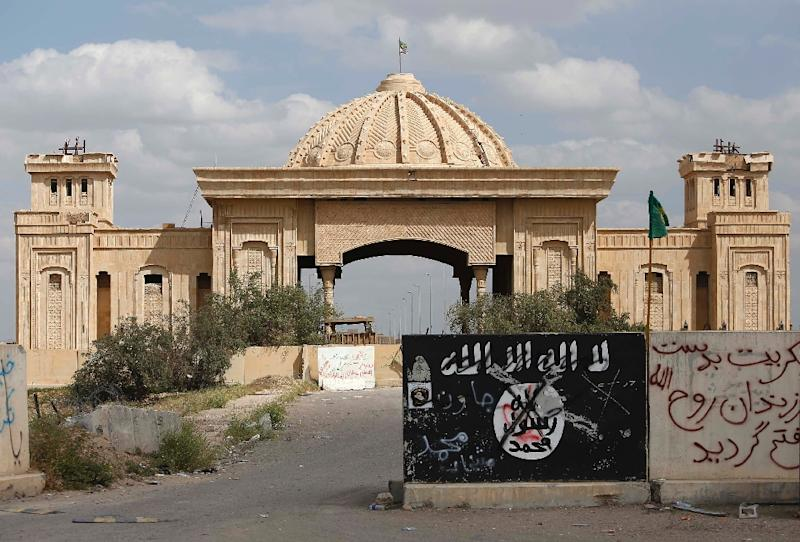 A general view taken on April 5, 2015 shows a defaced Islamic State group flag in front of the main gate of the palace of former Iraqi dictator Saddam Hussein in Tikrit after Iraqi forces retook the northern city from Islamist jihadists (AFP Photo/Mohammed Sawaf)