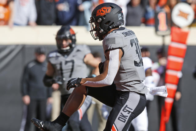 Oklahoma State running back Chuba Hubbard (30) runs into the end zone for a touchdown in the first half of an NCAA college football game against Kansas in Stillwater, Okla., Saturday, Nov. 16, 2019. (AP Photo/Sue Ogrocki)