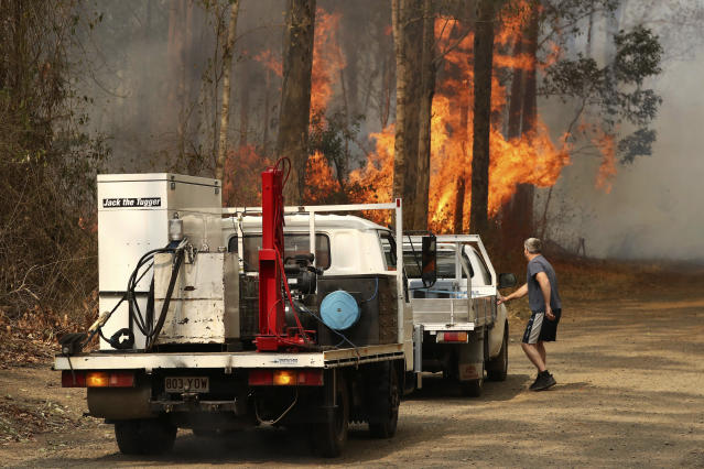 A local resident gets into his vehicle near a bushfire burning near Busbys Flat, Australia, Wednesday, Oct. 9, 2019. (Jason O'Brien/AAP Image via AP)
