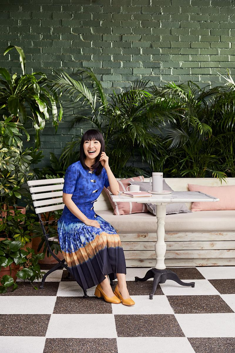 marie kondo sitting at small white table near dark green plants