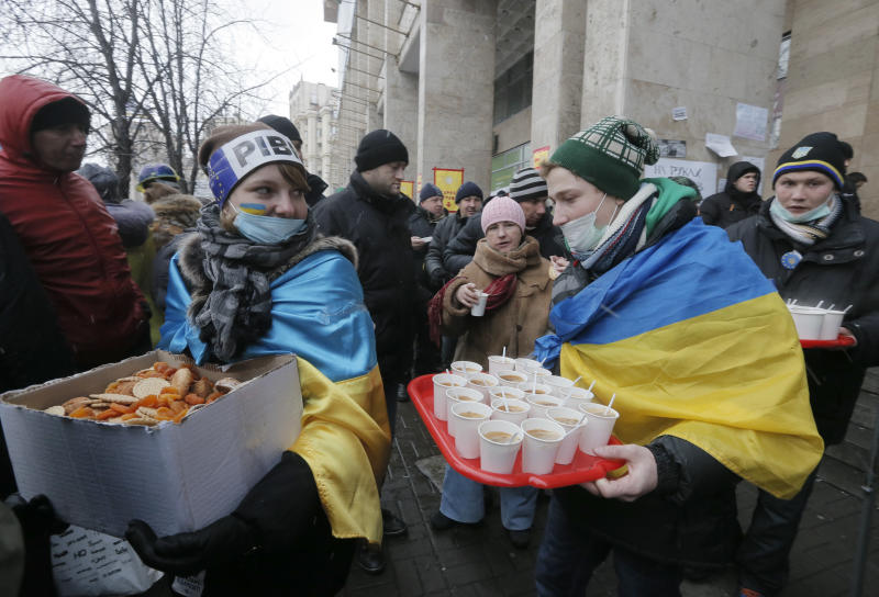 Volunteers offer free tea and food to pro-European Union activists at a mass rally in Independence Square in Kiev, Ukraine, Saturday, Dec. 7, 2013. As thousands of anti-government protesters kept their vigil in Ukraine's capital Saturday, officials sought to reduce their anger with assurances that Russian and Ukrainian presidents didn't discuss Ukraine joining a Russian-led customs union at a meeting this week. (AP Photo/Efrem Lukatsky)