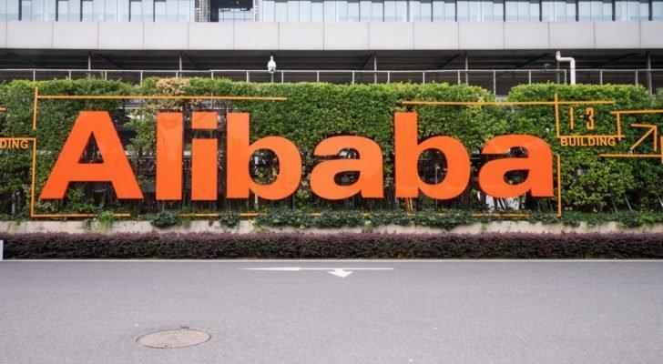 The Alibaba (BABA) logo featured outside of an office building with bushes in the background