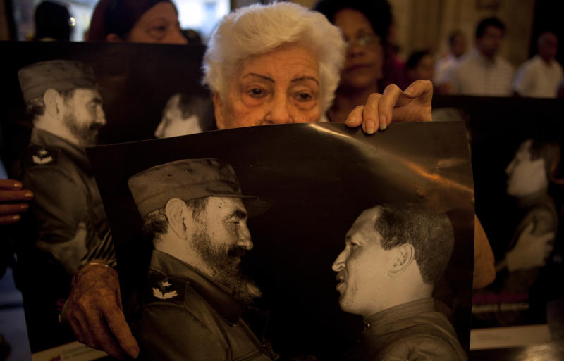 Parishioners hold posters that show Cuba's Fidel Castro, left, and Venezuela's President Hugo Chavez, during a Mass to pray for the recovery of Chavez at the Cathedral, in Havana, Cuba, Saturday, Jan. 12, 2013. The 58-year-old president is fighting a severe respiratory infection a month after he underwent cancer surgery in Havana, his government says. (AP Photo/Ramon Espinosa)