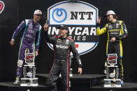 Will Power, center, of Australia, captures a photo as he walks to the podium after winning the IndyCar auto race at Indianapolis Motor Speedway, Saturday, Aug. 14, 2021, in Indianapolis. Romain Grosjean, left, of Switzerland, finished second and Colton Herta finished third. (AP Photo/Darron Cummings)
