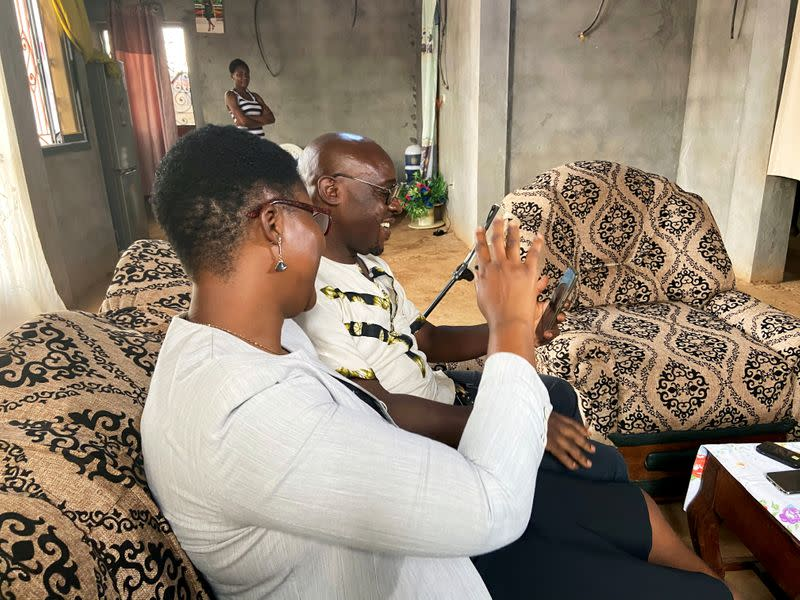 Roger Michel Kemkuining,  a teacher in an electrical engineering school, holds a video call with his son, Pavel Daryl Kem, 21, a student who is infected with the coronavirus in China as he sits with his wife Albertine at their house  in Douala