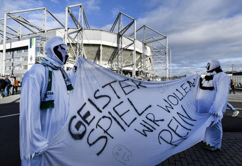 """Borussia fans dressed as ghosts hold a banner reading """"Ghost match - we want in"""" prior the German Bundesliga soccer match between Borussia Moenchengladbach and 1.FC Cologne in Moenchengladbach, Germany, Wednesday, March 11, 2020. It is the first Bundesliga match played behind closed doors without spectators due to the coronavirus outbreak. For most people, the new coronavirus causes only mild or moderate symptoms, such as fever and cough. For some, especially older adults and people with existing health problems, it can cause more severe illness, including pneumonia. (AP Photo/Martin Meissner)"""