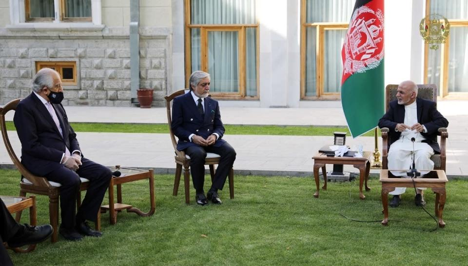 In this Wednesday, May 20, 2020 photo, Afghan President Ashraf Ghani, right, and fellow leader under a recently signed power-sharing agreement, Abdullah Abdullah, center, hold a meeting with U.S. peace envoy Zalmay Khalilzad aimed at resuscitating a U.S.-Taliban peace deal signed in February, at the Presidential Palace, in Kabul, Afghanistan. (The Presidential Palace via AP)