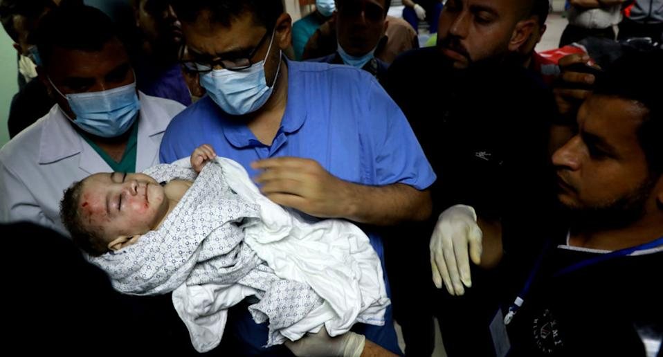A nurse at at Al-Shifa Hospital holds a baby who was pulled alive from under the rubble while seven other family members perished after an Israeli air strike at Al-Shati Refugee Camp on May 15, 2021.