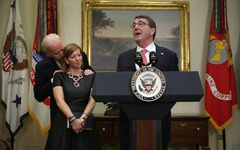 Former Defence Secretary Ashton Carter makes remarks as his wife Stephanie listens with Joe Biden - Credit: Getty