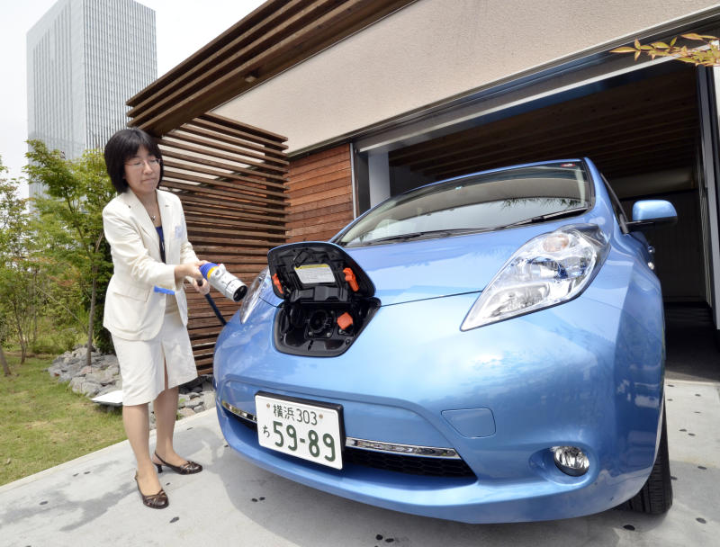 A Nissan employee demonstrates charging one of the country's Leaf electric vehicles using a smart home electricity supply cable in Yokohama, suburban Tokyo