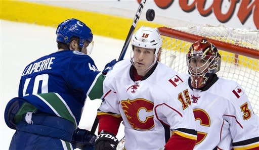 Vancouver Canucks center Maxim Lapierre (40) tries to get a shot past Calgary Flames right wing Tim Jackman (15) and Calgary Flames goalie Henrik Karlsson (35) during second period NHL hockey action at Rogers Arena in Vancouver, British Columbia, Saturday, March, 31, 2012. (AP Photo/The Canadian Press, Jonathan Hayward)
