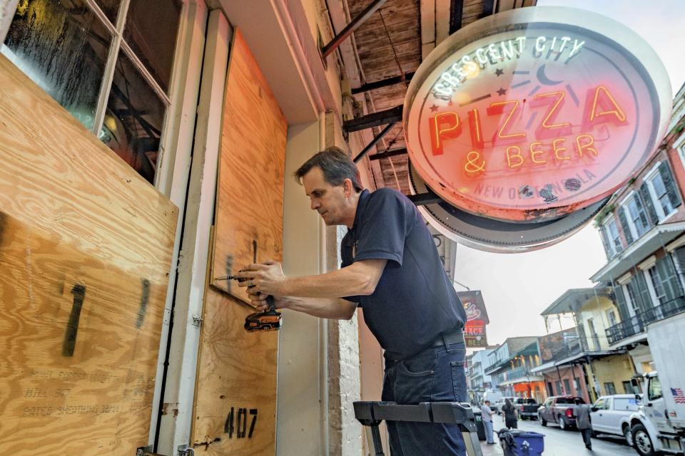 FILE - In this Aug. 28, 2021 file photo, Michael Richard of Creole Cuisine Restaurant Concepts boards up Crescent City Pizza on Bourbon Street in the French Quarter before landfall of Hurricane Ida in New Orleans. Small businesses from Louisiana to Connecticut are facing an uncertain recovery after being walloped by Ida and its residual rains and flooding last week. Days after the destruction, they're reaching out to clients and staff, assessing damage and trying to plan for the way forward.(AP Photo/Matthew Hinton, File)