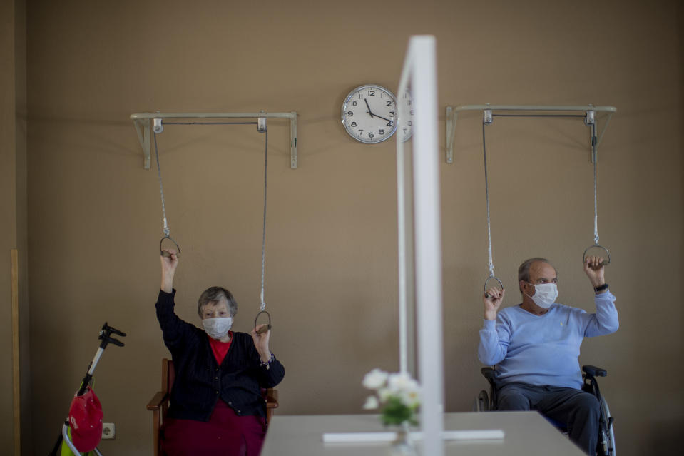 Residents wear face masks to protect against the spread of coronavirus as they exercise at DomusVi nursing home in Leganes, Spain, Wednesday, March 10, 2021. (AP Photo/Manu Fernandez)