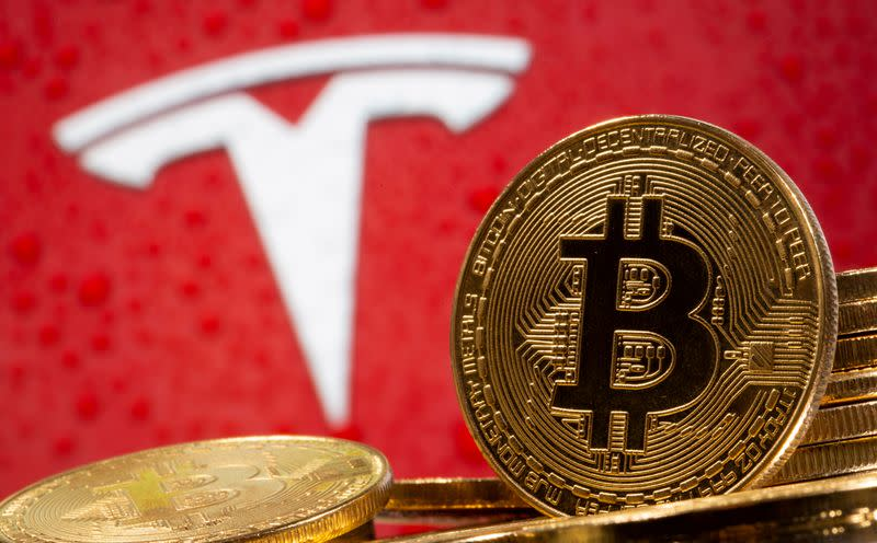 FILE PHOTO: FILE PHOTO: FILE PHOTO: Representations of virtual currency Bitcoin are seen in front of Tesla logo in this illustration