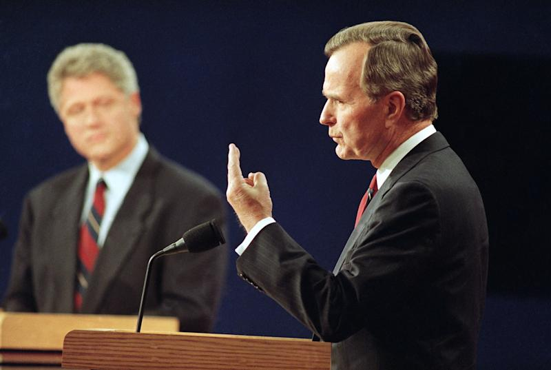 With Democratic presidential candidate Bill Clinton looking on at left, President George Bush speaks during the first presidential debate in St. Louis, Mo., Oct. 12, 1992. (AP Photo/Bill Waugh)