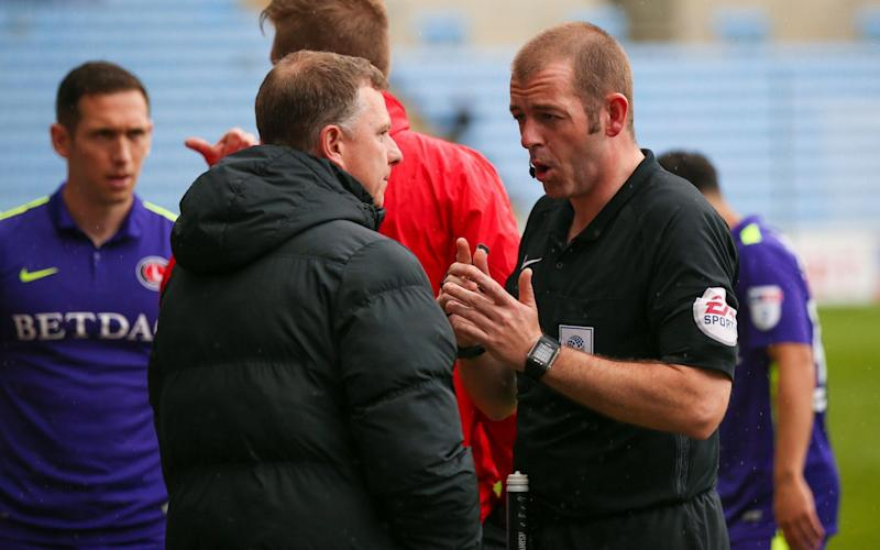 The referee and Coventry manager Mark Robins chat about the situation - Credit: Rex