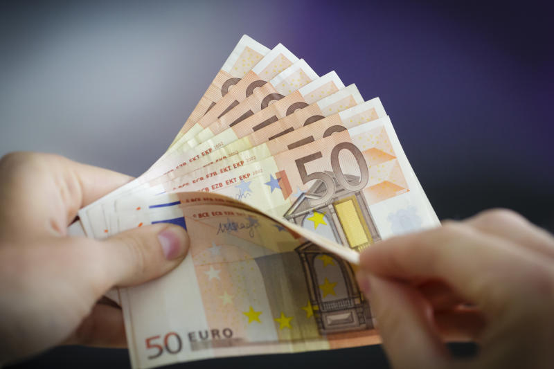 Berlin, Germany - August 03: In this Photo Illustration a person holds Euro banknotes on August 03, 2016 in Berlin, Germany. (Photo Illustration by Thomas Trutschel/Photothek via Getty Images)