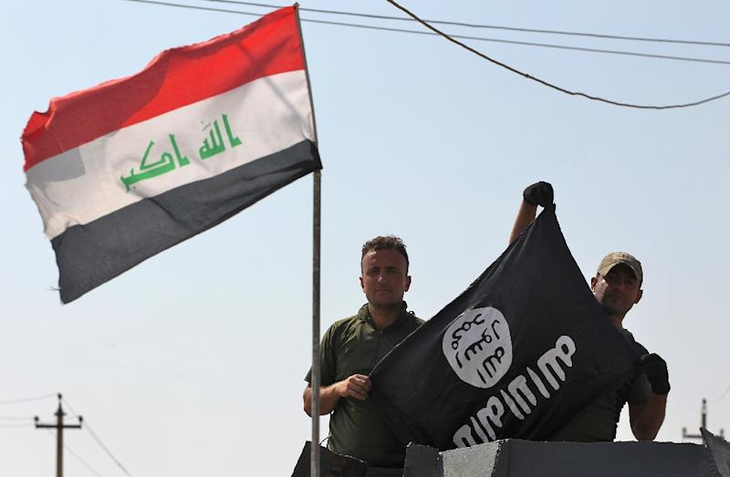 Members of the Iraqi forces hold a flag of the Islamic State group upside down in the northern Iraqi town of Sharqat on September 22, 2017