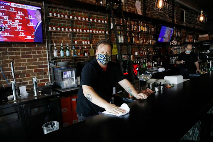 An employee at Carmines Ybor Italian restaurant wipes off the bar while awaiting patrons on June 26, 2020 in Tampa, Florida.