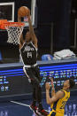Los Angeles Clippers' Terance Mann (14) dunks against Indiana Pacers' Jeremy Lamb (26) during the second half of an NBA basketball game, Tuesday, April 13, 2021, in Indianapolis. (AP Photo/Darron Cummings)