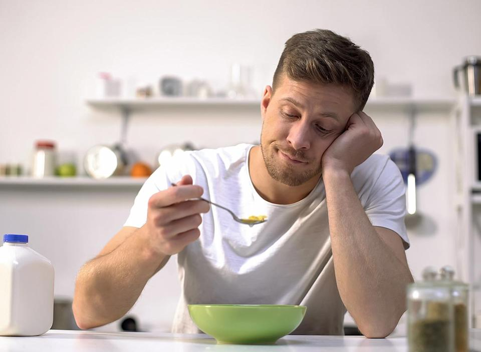 bored man eating bowl of cereal in kitchen
