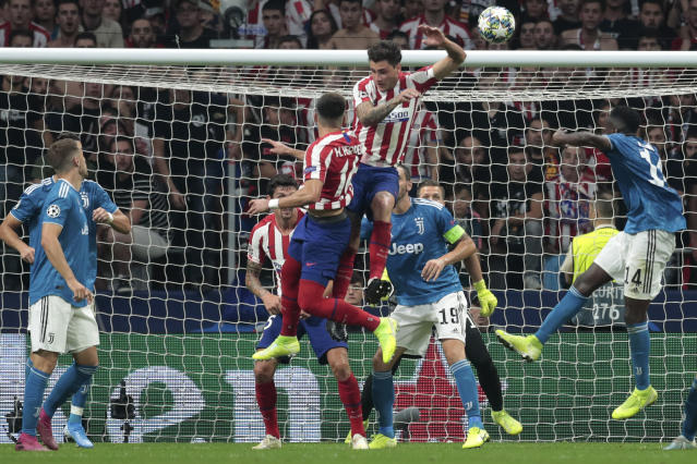 Atletico Madrid's Hector Herrera, center left jumping, heads the ball into the net to score his side's second goal during the Champions League Group D soccer match between Atletico Madrid and Juventus at the Wanda Metropolitano stadium in Madrid, Spain, Wednesday, Sept. 18, 2019. (AP Photo/Bernat Armangue)