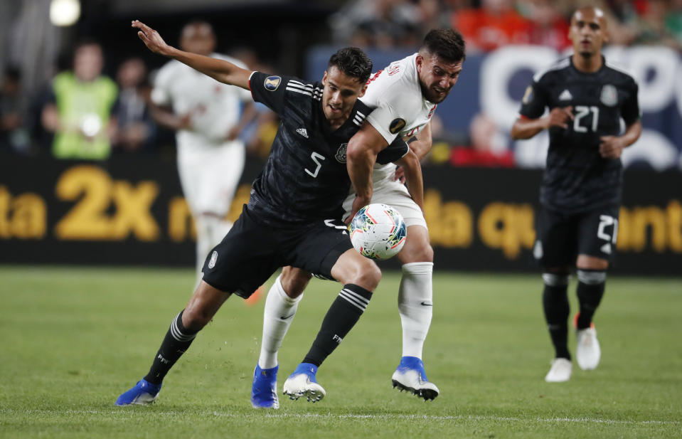Mexico defender Diego Reyes, left, fights for control of the ball with Canada forward Lucas Cavallini during the first half of a CONCACAF Gold Cup soccer match Wednesday, June 19, 2019, it Mile High Stadium in Denver. (AP Photo/David Zalubowski)