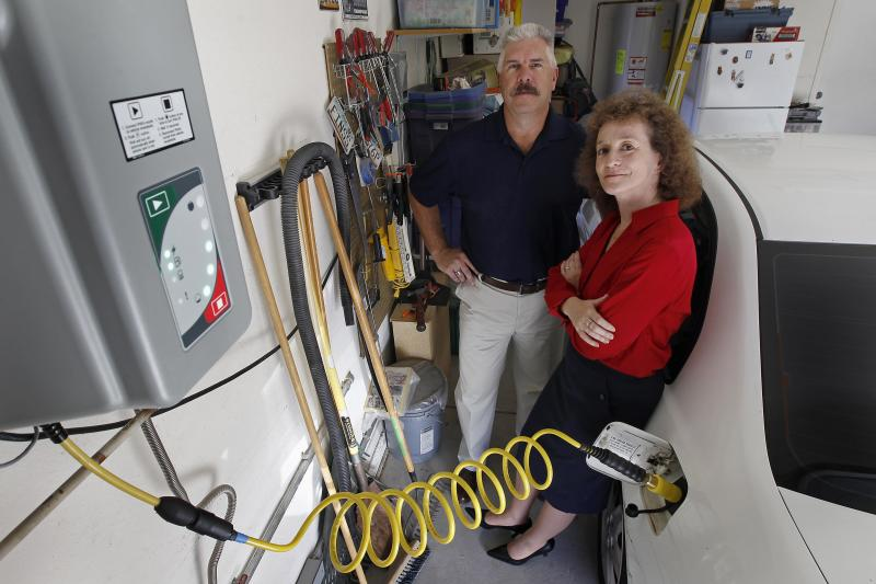 Connie and Travis Jones pose with their 2003 natural gas powered Honda Civic and natural gas home refueling station located on the garage wall of their home in Chandler, Arizona, October 3, 2013.Home refueling units, which tap into a house natural gas main and compress the fuel so it can fill a vehicle tank overnight, have been available for years. With natural gas at $1.40 per equivalent gallon, it costs the Joneses $30 to drive their Honda Civic GX 1,200 miles (1,930 km) each month, about $130 less than an average gasoline car covering the same distance. Picture taken October 3, 2013. To match Insight NATURALGAS/HOME-REFUELING REUTERS/Ralph D. Freso (UNITED STATES - Tags: TRANSPORT BUSINESS ENERGY)
