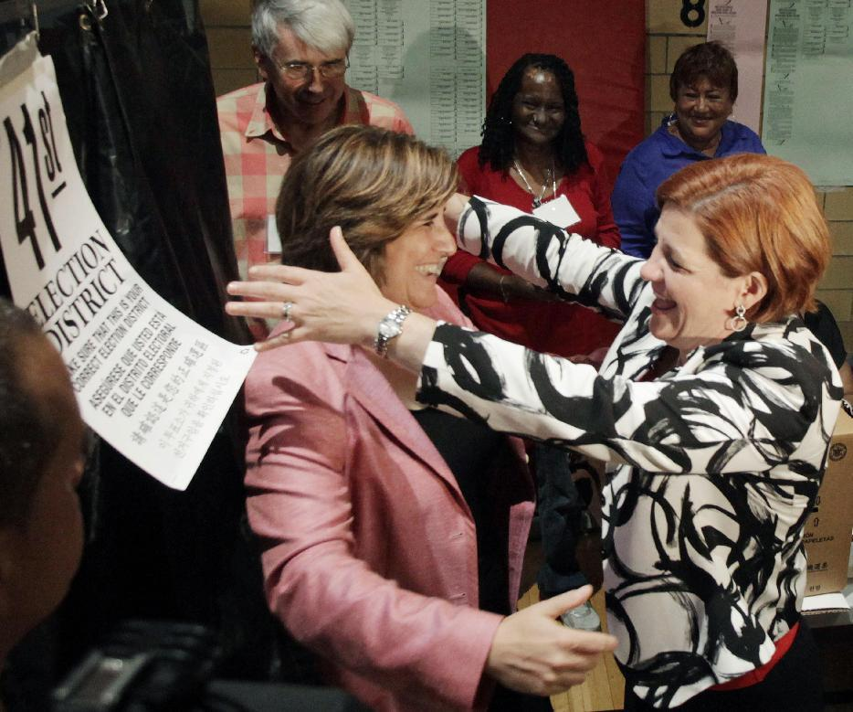 City Council Speaker and New York City Democratic mayoral hopeful Christine Quinn, right, embraces her wife, Kim Catullo, after Catullo voted in the primary election, Tuesday, Sept. 10, 2013, in New York. Quinn led the polls for most of the year but has seen support disappear as her rivals linked her to the bitter debate to let Mayor Michael Bloomberg run for a third term in 2009. (AP Photo/Mark Lennihan)